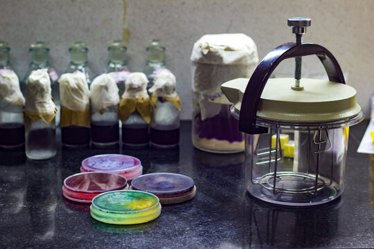 Anaerobic gas jar along with culture plates containing culture media placed on desk of a microbiology laboratory