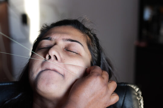 painful plucking and removal of upper lip hairs of a lady with threading. epilation cosmetic procedure in beauty parlour.