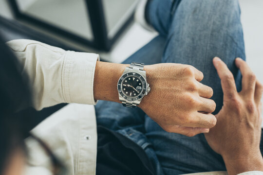 fashionable wearing stylish looking at luxury watch on hand check the time at workplace.concept for managing time organization working,punctuality,appointment