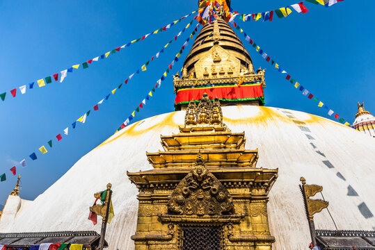 Tower of the Boudhanath Stupa decorated with flags in Kathmandu, Nepal.