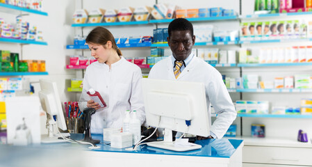 Two professional male and female pharmacists working behind counter in modern pharmacy