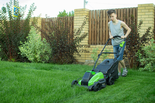 A teenager mows the lawn with a lawn mower.