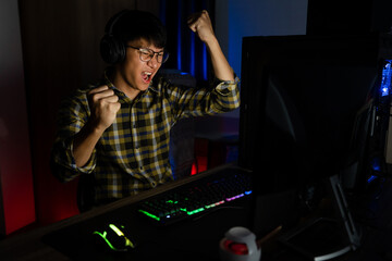 Excited asian man pro gamer sitting at the table, playing and Winning in online video games on a computer and smartphone, technology gaming cyber or e-sport championship concept