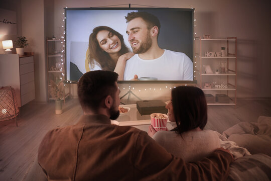 Young couple watching movie at home