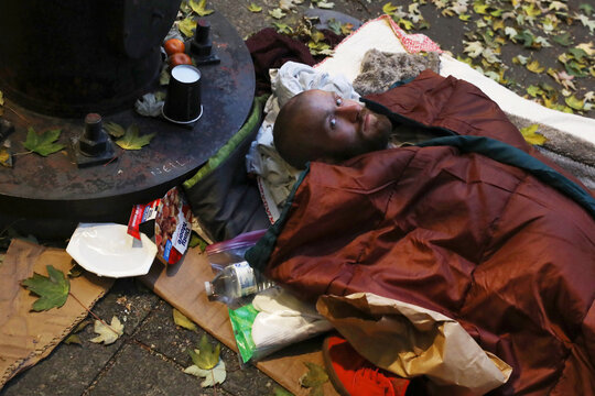 A homeless man stares while laying in his sleeping bag on a sidewalk in Portland, Oregon