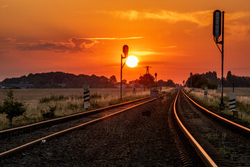 sun is setting over the railroad tracks