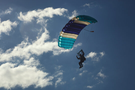 Skydiver pilots a parachute canopy, close-up.