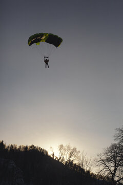 Silhouette of a BASE jumper under a parachute canopy against the background of a hillside in the evening light.
