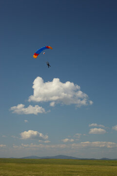 Bright parachute flying over green field on a background of blue sky and clouds.