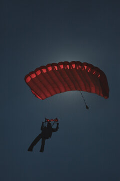 Skydiver with a red parachute in backlight solar illumination on a background of dark sky, the image in low key.
