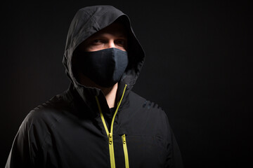 The man in the mask puts on a glove. Preparation for robbery or hacking