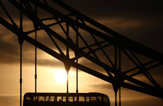 Passengers travel on a bus across the Tower Bridge as the sun rises during the morning rush hour in London