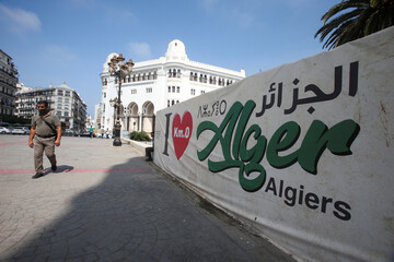 """A man walks past an """"I love Algiers"""" banner near the central post office in Algiers"""