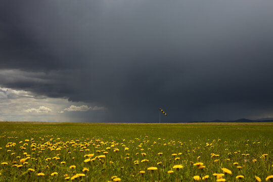 Green meadow with a windsock in the vicinity of the airfield on the background of black stormy sky.
