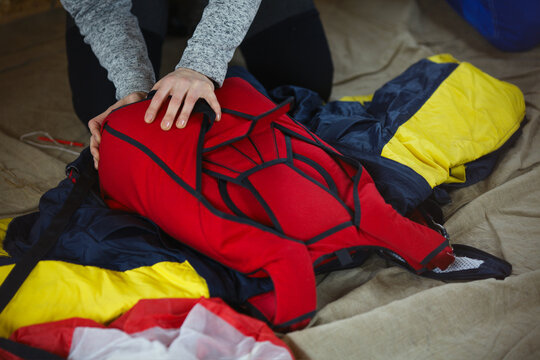 Wing suit and a parachute satchel during packaging, close-up.