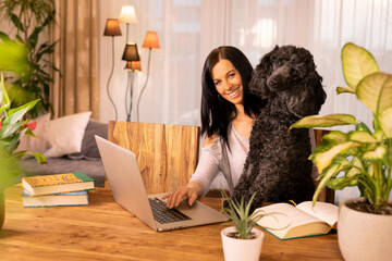 Young female working on her laptop computer with her poodle dog in a home office.