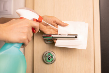 closeup of a woman disinfecting the door handle by spraying a sanitizer from a bottle