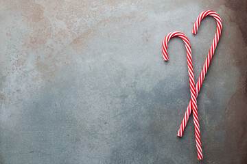 Christmas candy cane lied on blue background. Flat lay and top view.