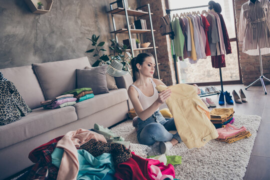 Full body focused girl house wife prepare for garage sale auction look pack her used dressing clothes pile stack sit floor carpet legs crossed folded in house indoors