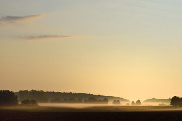 In a wide landscape in Bavaria at dawn the fog pulls up over fields and trees.