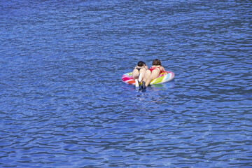 Two young girls swimming on air mattress in the sea