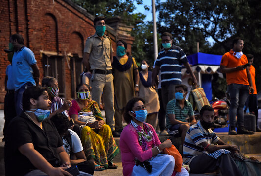 Devotees wearing protective face masks gather to perform Tarpana on the banks of the Ganges river to honour the souls of their departed ancestors during the auspicious day of Mahalaya in Howrah