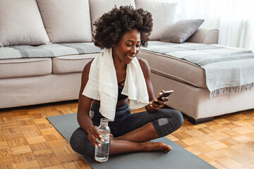 Beautiful young woman wiping sweat with a towel, exhausted after the daily training. Happy smiling african american woman with water and smartphone doing sports at home