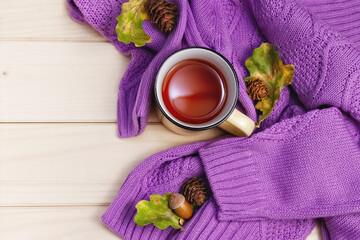 autumn flat lay purple sweater, metal tea mug with oak leaves and pine cones