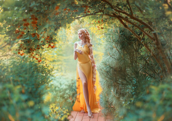 Beautiful young blond woman with very long hair that is braided. The girl is dressed in a seductive yellow dress with a slit on the leg. Fashion model posing against the backdrop of an autumn garden.