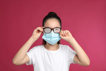 Little girl wiping foggy glasses caused by wearing medical face mask on pink background. Protective...