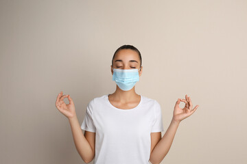 Woman in protective mask meditating on beige background. Dealing with stress caused by COVID‑19...