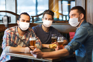 male friendship, leisure and pandemic concept - men or friends in face protective medical masks for protection from virus drinking beer and taking picture with smartphone selfie stick at bar or pub