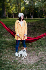 young woman wearing yellow raincoat standing next to hammock with her jack russell dog. autumn season. camping concept