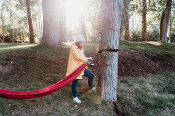 young woman wearing yellow raincoat preparing hammock to relax. Camping outdoors. autumn season