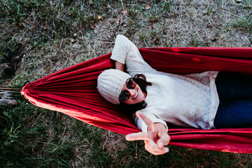 young woman relaxing in orange hammock. Camping outdoors. autumn season at sunset