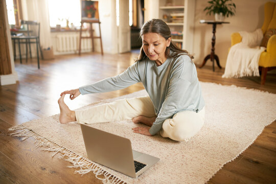Indoor image of flexible active mature gray haired female sitting on floor in front of open laptop, stretching legs during online yoga lesson, watching live video with professional instructor
