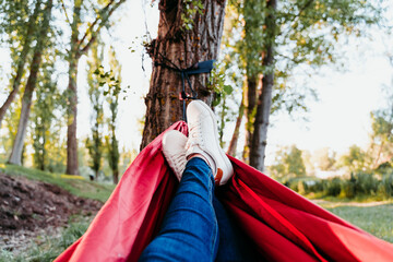 unrecognizable feet of woman relaxing in orange hammock. Camping outdoors. autumn season at sunset. POV