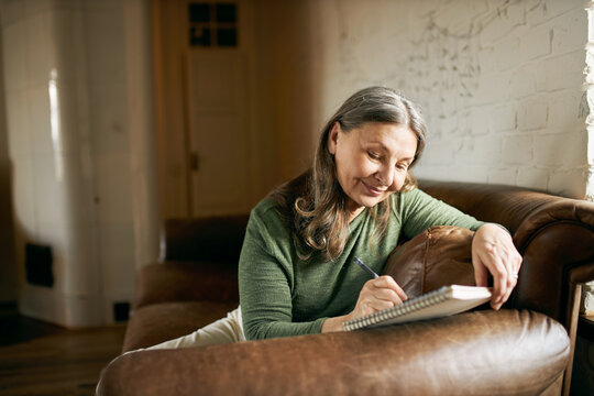 Creative beautiful middle aged woman with long gray hair sitting on comfortable leather couch with notebook handwriting poems, drawing or making list to do, having dreamy facial expression, smiling