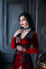 Beautiful young sexy woman vampire in medieval dark castle. Red gothic evening dress. Black wavy hair. Backdrop vintage room. A girl holding a glass of bloody wine in her hands. Image queen of night