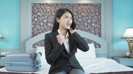 Smiling Asian Thai business woman using a smartphone or mobile phone in bedroom at hotel in technology device concept. Lifestyle people.