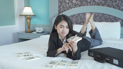 Rich business Asian Thai woman counting money to save banknote in financial account and investment concept on bed in bedroom in hotel.