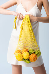 cropped view of woman in silk dress holding string bag with fruits on white, ecology concept