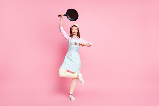 Full length body size view of her she nice attractive pretty focused housewife holding in hands kitchenware utensil posing meditating asana yoga zen isolated over pink pastel color background