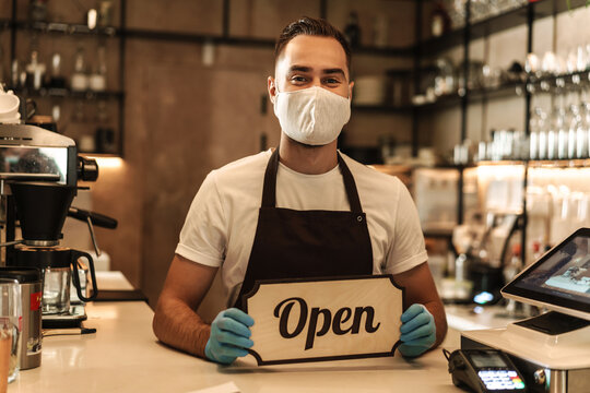 Man barista wearing medical mask showing open sign