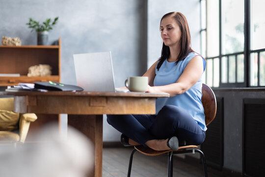 Beautiful relaxing businesswoman sitting near table in lotus pose working on laptop