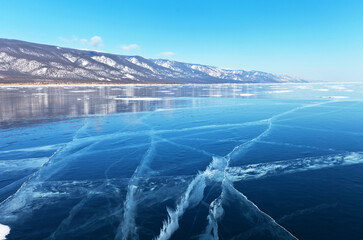 Landscape typical of winter Baikal Lake with beautiful blue smooth ice and snow-capped coastal mountains in February. Natural background. Winter ice travel on the lake (focus on ice)