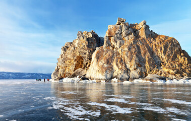 Baikal Lake in March. A group of tourists walk on the ice near the Shamanka Rock on Olkhon Island near the village of Khuzhir. Winter ice travel on the frozen lake. Beautiful landscape