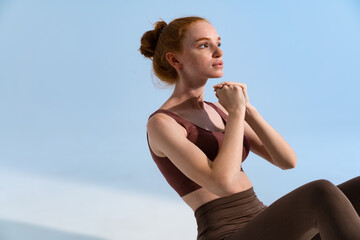 Photo of athletic focused sportswoman doing exercise while working out
