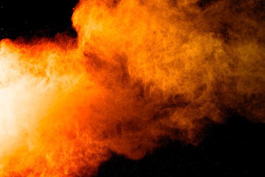 Abstract orange powder explosion. Closeup of orange dust particle splash isolated on black background.