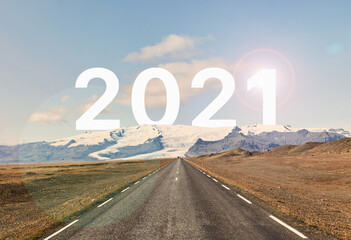 The word 2021 is written behind a glacier and an empty asphalt road against a golden sunset and beautiful blue sky. The year 2021 is written behind the glacier.